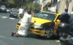 Ce taximan emprunte un sens interdit pour rallier la route principale, un passant s'y oppose avec la plus grande énergie.